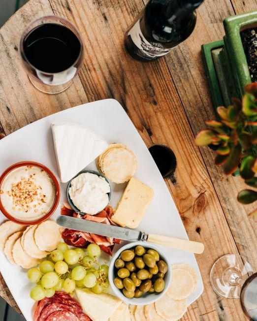 Food Wine Shopping Italy. Photography credit Melissa Walker White plate with cheese, ham, olives and fruits with wine a bottle of wine and glass on the side