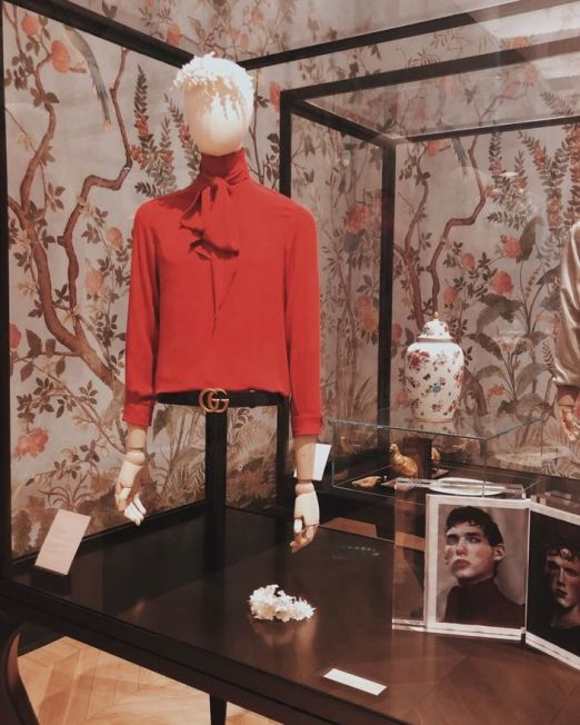 Fashion Textile History Experience. Red shirt on mannequin with floral wallpaper on the back in museum called gucci garden