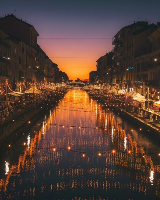 Italian City Tour by Night. Canal of Milan by night with bright lights. Photography Credit: Cristina Gottardi